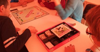 Uczestnicy Domu grają w grę planszową przy stole